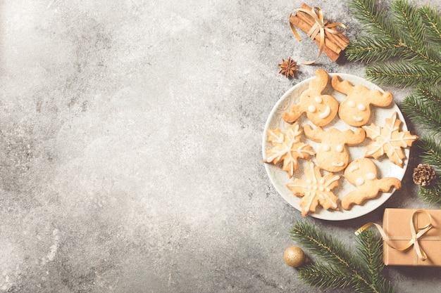 크리스마스 배경입니다. 전나무 가지, 선물, 과자, 쿠키, 밝은 콘크리트 배경에 계피와 함께 크리스마스 구성