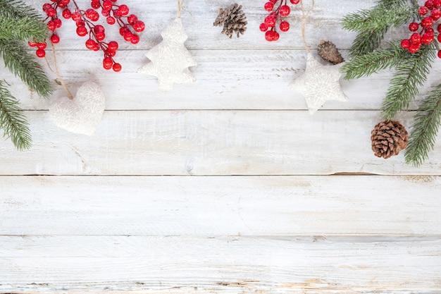 クリスマスの背景 - クリスマス飾りの要素と飾り雪片と白い木のテーブルに素朴。クリエイティブなフラットなレイアウトと、境界線とコピースペースのデザインによるトップビューの構図。