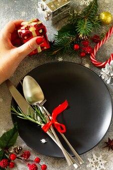 クリスマスの背景クリスマスの装飾テーブル女性の手はお祝いのテーブルの黒いプレートを提供しています