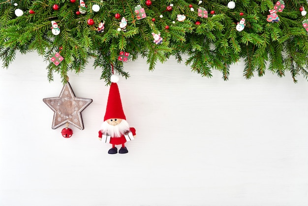 Christmas background. christmas fir tree branch with santa on white wooden background. cop