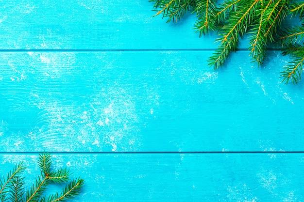 クリスマスの背景。コピースペースのある青い素朴な木の板にクリスマスのモミの木の枝。