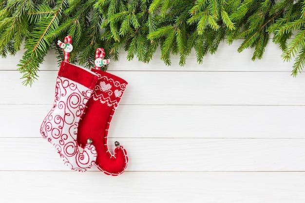 クリスマスの背景。コピースペースと白い木の板の背景にクリスマスの靴下とクリスマスのモミの木