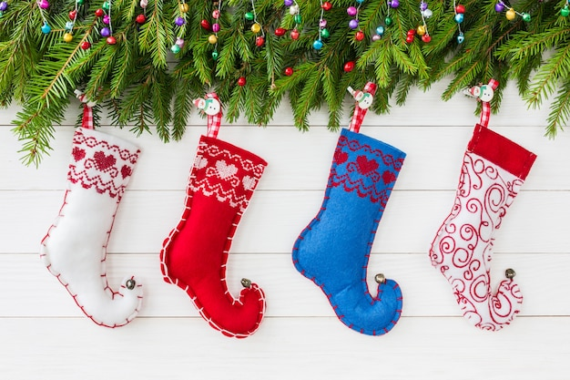 Рождественский фон рождественская елка с украшениями, красочные рождественские носки на фоне белой деревянной доске с копией пространства