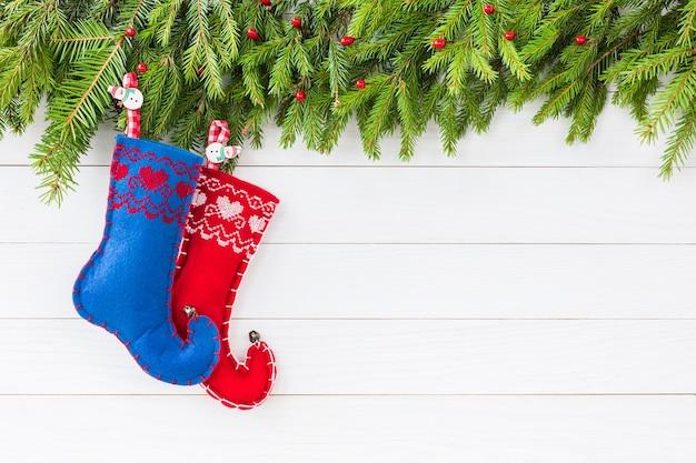 クリスマスの背景。装飾が施されたクリスマスのモミの木、コピースペースと白い木の板の背景に赤と青のクリスマスソックス。