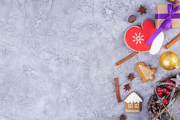 Christmas background. christmas gift, toys, gingerbread cookies, spices and decorations on wooden table. top view