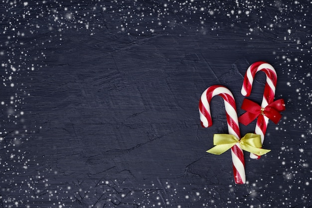 Christmas background. christmas greeting card with christmas tree and candy cane. copyspace, dark background