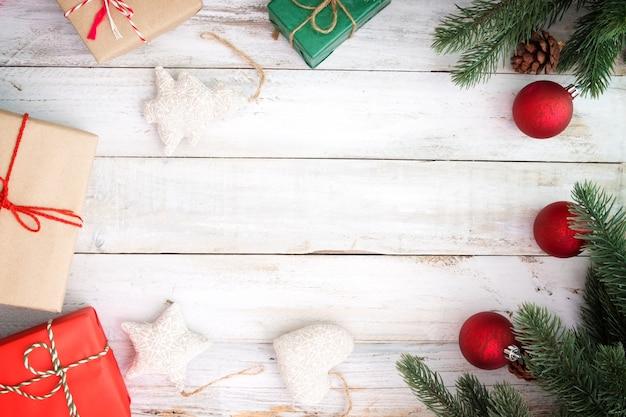 クリスマスの背景 - クリスマスプレゼントのギフトボックスと白い木製の背景に要素を飾る。クリエイティブなフラットなレイアウトと、境界線とコピースペースのデザインによるトップビューの構図。