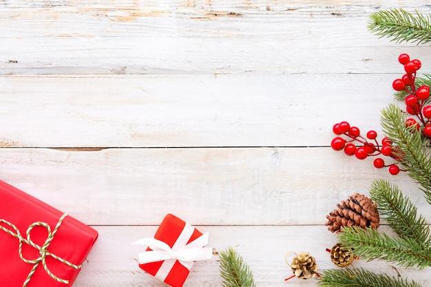 クリスマスの背景 - クリスマスプレゼント赤のギフトボックスと白の木製の背景に要素を飾る。クリエイティブなフラットなレイアウトと、境界線とコピースペースのデザインによるトップビューの構図。