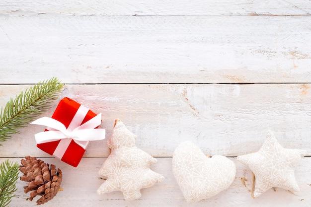 クリスマスの背景 - クリスマスプレゼント赤のギフトボックスと白い木製の背景に要素を飾る。クリエイティブなフラットなレイアウトと、境界線とコピースペースのデザインによるトップビューの構図。