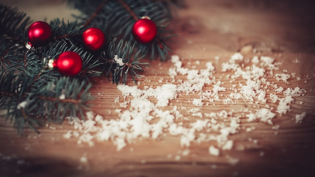Christmas background.christmas tree branch with balls on wooden background.photo with place for text
