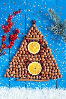 크리스마스 배경입니다. 크리스마스 트리 모양의 견과류, 딸기와 향신료