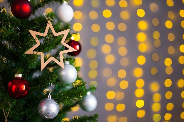 Christmas background - christmas tree with colorful balls and golden lights at home