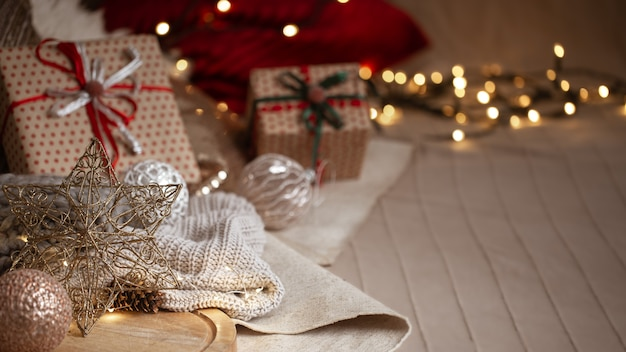 Рождественский фон композиция из декоративной звезды, гирлянды, подарочных коробок, деталей домашнего декора и размытых огней копирует пространство.
