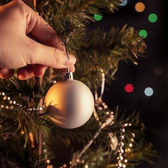 クリスマスの背景の概念-輝く光のスポット、ぼやけた暗い黒の背景、コピースペース、クローズアップでクリスマスツリーにぶら下がっている美しい装飾の安物の宝石。
