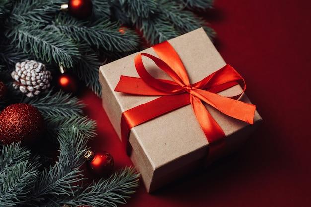 赤いボールと赤い背景に松ぼっくりの枝とクリスマスの背景コンセプトギフトボックス