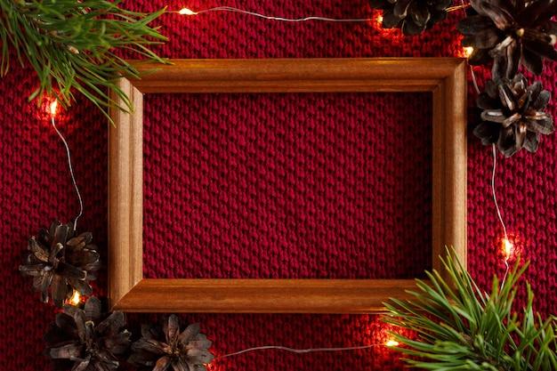 クリスマスの背景セーターのニットの質感の上に横たわるコーンフレームと花輪