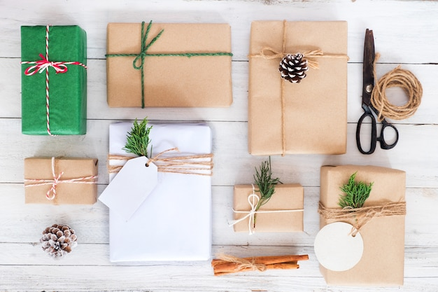 Christmas background - craft and handmade christmas present gift boxes and rustic decoration on white wooden board. creative flat layout and top view composition