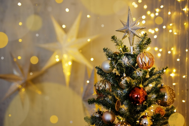 Christmas background - decorated christmas tree with festive garland lights and paper stars
