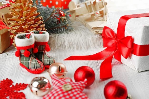 クリスマスの背景。装飾、コーン、白い木製の背景のギフトボックス