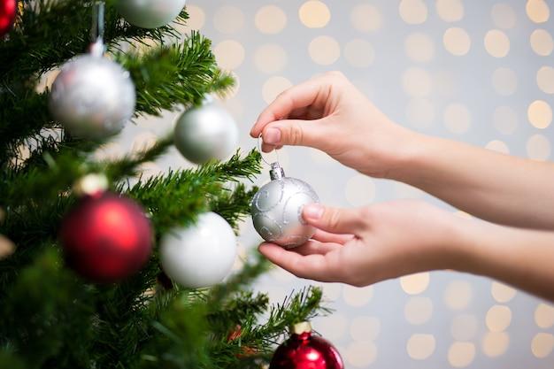 Christmas background - female hands decorating christmas tree