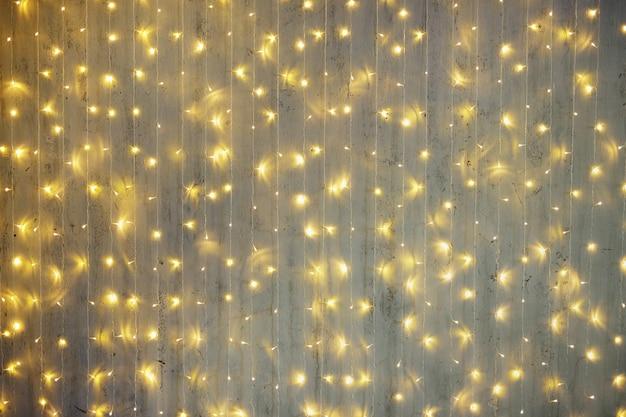 クリスマスの背景-お祝いの花輪は灰色の壁の上のライトを導いた