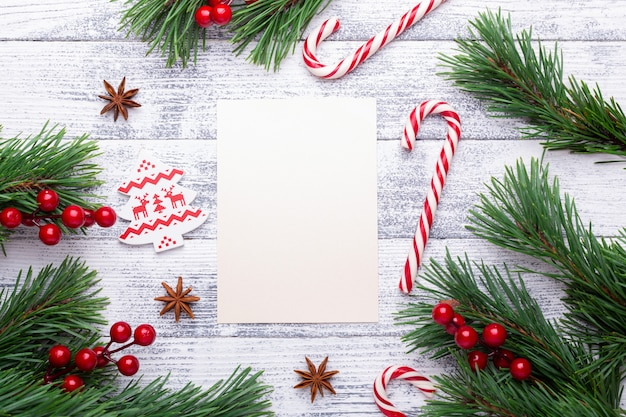 Christmas background. fir branches, candy cane and gifts on a light wooden background.