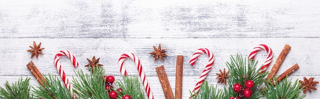 Christmas background. fir branches, candy cane and gifts on wooden background horizontal banner snow effects