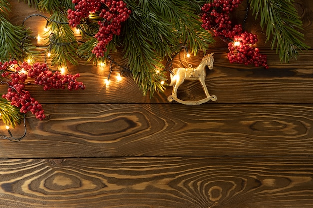Christmas background fir branches twigs with red berries toy golden horse on brown wooden planks