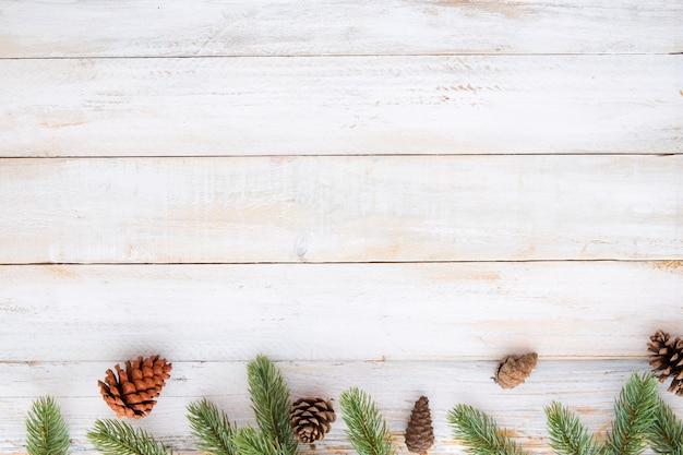 クリスマスの背景 - モミの葉と松の小片は、白い木のテーブルに素朴な要素を飾る。クリエイティブなフラットなレイアウトと、境界線とコピースペースのデザインによるトップビューの構図。