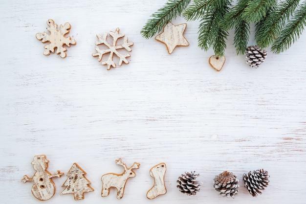 クリスマスの背景 - モミの葉と白い木のテーブルに飾る素朴な要素。
