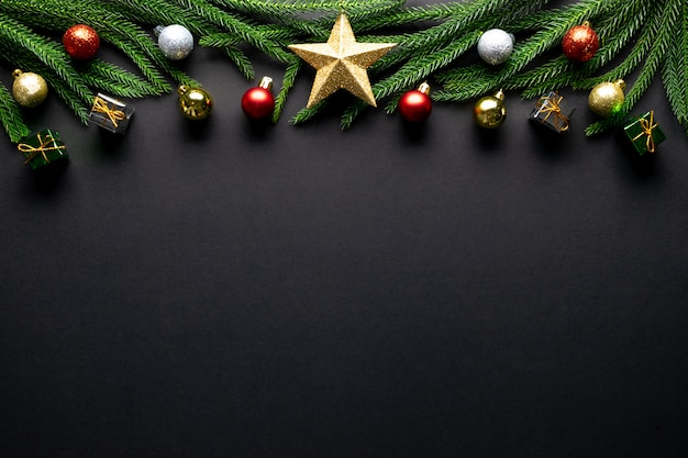 Christmas background. fir tree branches, red decorations on black background