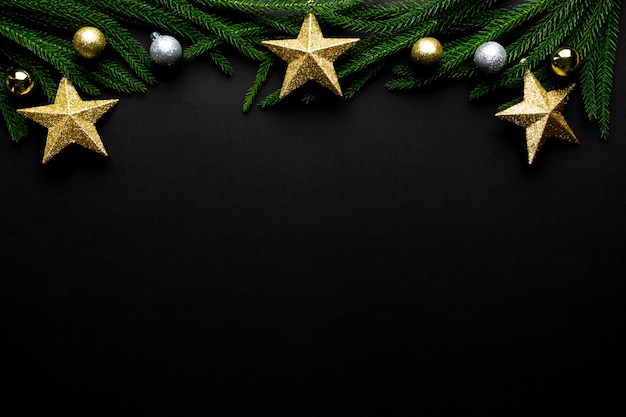 Christmas background. fir tree branches, star decorations on black background. flat lay, top view, copy space.