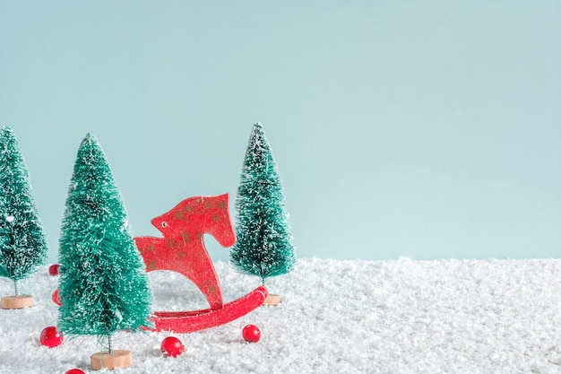 クリスマスの背景。雪の背景に馬のおもちゃと赤い果実とモミの木