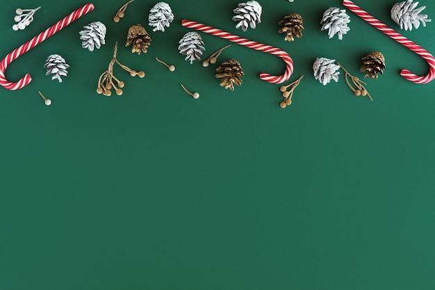 クリスマスの背景。緑の背景にモミの木の円錐形、花輪、赤い装飾と白いボールのフラットレイと上面図。コピースペースでクリスマス、冬、新年のコンセプト