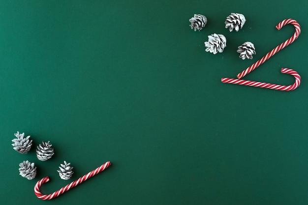 クリスマスの背景。花輪、赤い装飾、緑の背景に白い雪の円錐形のフラットレイと上面図。コピースペースでクリスマス、冬、新年のコンセプト