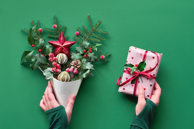 Christmas background flat lay on green paper. female hand holding veneer cone with fir and holly, candy canes and berries. another hand hold wrapped pink gift with red ribbon.