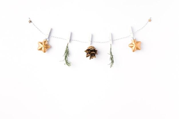 크리스마스 배경입니다. 흰색 배경 위에 금색 공과 전나무 나뭇가지로 만든 화환의 평평한 위치. 크리스마스, 겨울, 새 해 개념입니다. 상위 뷰, 복사 공간
