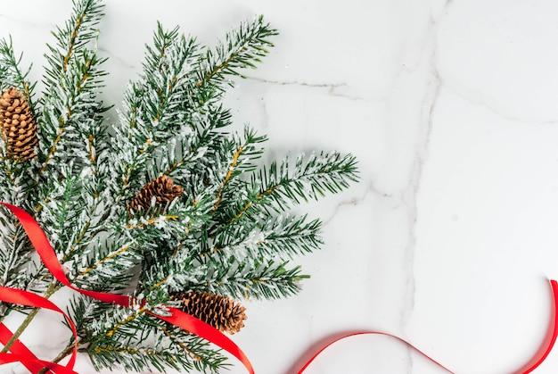 グリーティングカードのクリスマス背景。白い大理石の背景にお祝いの赤いリボンと雪の影響でクリスマスツリーの枝