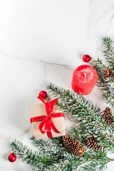 グリーティングカードのクリスマス背景。お祝いの赤いリボン、松ぼっくり、ギフトボックス、白い大理石の背景の上のろうそくと雪の影響でクリスマスツリーの枝