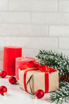 グリーティングカードのクリスマス背景。お祝いの赤いリボン、松ぼっくり、ギフトボックス、キャンドル、白い大理石の背景に雪の影響でクリスマスツリーの枝