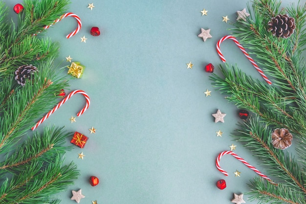 Christmas background from christmas candies, branches of a christmas tree, toys, sparkles and stars