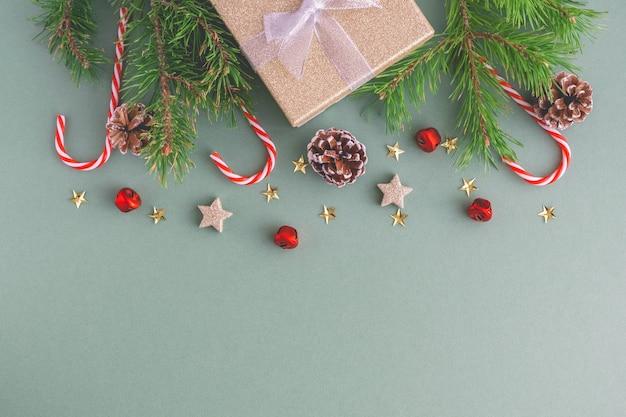 クリスマスキャンディー、クリスマスツリーの枝、おもちゃ、ギフトボックス付きコーンからのクリスマスの背景