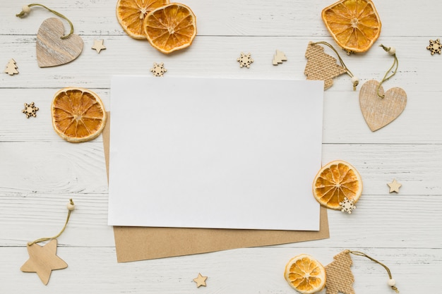 Christmas background from dried oranges, christmas decorations and empty white card for greetings on a wooden table. stars and hearts. copyspace