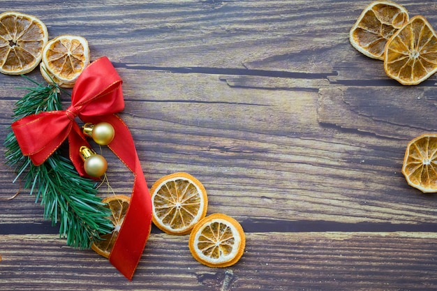 Christmas background from dried oranges, pine twig and red bow on a wooden table