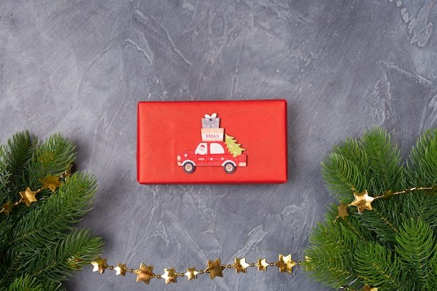Christmas background. gift box, fir tree, wooden toy car with santa and text x-mas. concept. flat lay, copy space