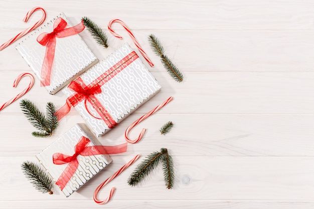 Christmas background. gifts, fir tree branches, red decorations on white wooden background. flat lay, top view, copy space
