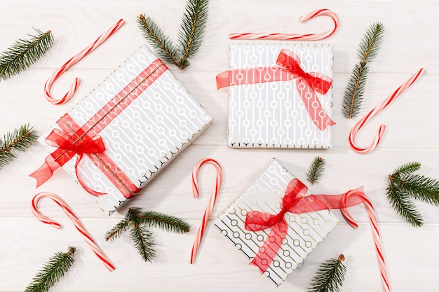 Christmas background. gifts, fir tree branches, red decorations on white wooden background. flat lay, top view
