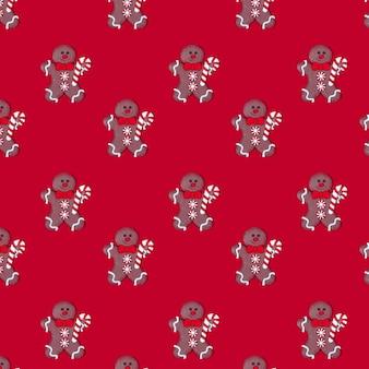 クリスマスの背景赤い背景のパターンで彼の手にキャンディーを持つジンジャーブレッドマン。