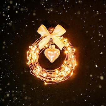 Рождественский фон. светящийся круг из гирлянды в виде елочной игрушки на черном фоне с блестками. праздничная концепция дизайна.