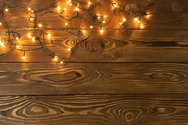 Christmas background glowing garlands on brown wooden planks one side copy space flat lay